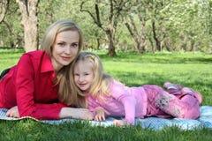 Mère avec le mensonge de descendant sur l'herbe Photo libre de droits