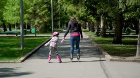 Mère avec le patinage de rouleau de fille en parc clips vidéos