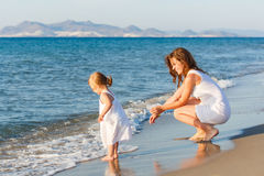 Mère avec le petit descendant sur la plage Photographie stock