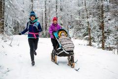 Mère avec le promeneur de bébé appréciant l'hiver dans la forêt, temps de famille image stock