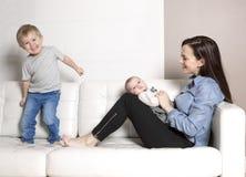 Mère avec le sofa de bébé Photo stock