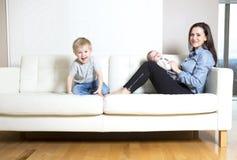 Mère avec le sofa de bébé Images stock