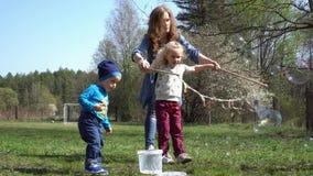 Mère avec les bulles de soufflement de fils et de fille en parc Mouvement de cardan banque de vidéos