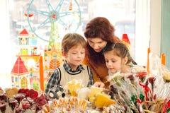 Mère avec les enfants heureux dans le magasin de bonbons image stock