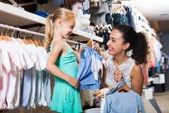 Mère avec les vêtements de achat de fille Photos stock