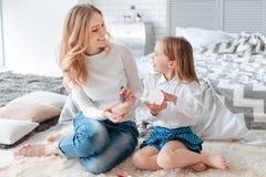 Mère avec plaisir et fille gaies regardant l'un l'autre Photo stock