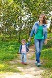 Mère avec sa fille se cachant derrière un arbre Photos libres de droits