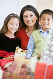 Mère avec ses cadeaux de Noël de fixation de famille Photo libre de droits