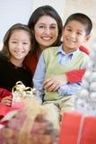 Mère avec ses cadeaux de Noël de fixation de famille Photos stock