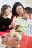Mère avec ses cadeaux de Noël de fixation de famille Photographie stock