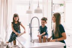 Mère avec ses enfants jouant dans l'évier de cuisine photographie stock libre de droits