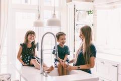 Mère avec ses enfants jouant dans l'évier de cuisine images libres de droits