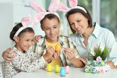 Mère avec ses oeufs de peinture de fils et de fille pour Pâques image libre de droits