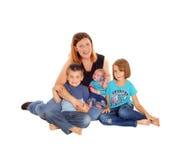 Mère avec ses trois enfants s'asseyant sur le plancher Images libres de droits