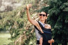 Mère avec son bébé dans le transporteur de bébé prenant le selfie avec le smartphone ou le blogger images stock