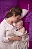Mère avec son bébé dormant dans le lit Photographie stock