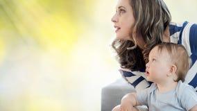 Mère avec son enfant de garçon regardant fixement sur des rayons de lumière Image libre de droits
