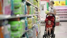 Mère avec son garçon dans la voiture d'enfant dans le supermarché banque de vidéos