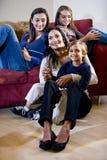 Mère avec trois enfants détendant sur la salle de séjour images stock