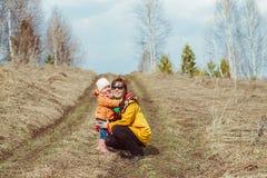 Mère avec un enfant marchant dans la forêt d'automne photographie stock