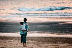 Mère avec un enfant observant un océan Photographie stock