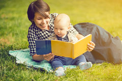 Mère avec une lecture d'enfant en parc Image libre de droits