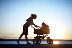 Mère avec une poussette Image stock
