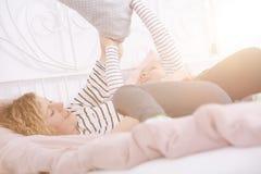 Mère ayant le combat d'oreiller avec sa fille photo libre de droits