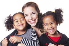 Mère blanche avec la famille noire d'enfant posant sur un studio blanc de fond photo stock