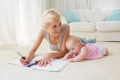 Mère blonde de sourire avec son écriture de bébé sur un cahier Photographie stock libre de droits