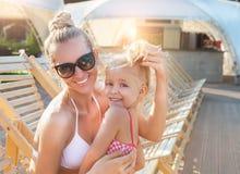 Mère blonde heureuse balayant de longs cheveux de sa fille près du p photographie stock