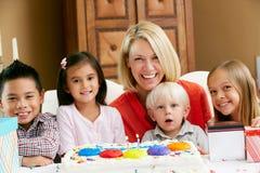 Mère célébrant l'anniversaire de l'enfant avec des amis Photographie stock libre de droits