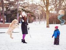 mère caucasienne blanche avec l'enfant de garçon d'enfant en bas âge jouant avec le grand grand chien dehors le jour d'hiver Image libre de droits