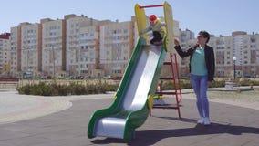 Mère caucasienne et sa petite fille espiègle jouant sur un terrain de jeu coloré, nouveau et moderne, tour en bas d'une colline clips vidéos