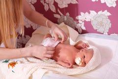 Mère changeant un fils nouveau-né de couche-culotte Image libre de droits