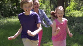 Mère chassant des enfants le long de chemin de région boisée clips vidéos