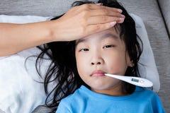 Mère chinoise asiatique mesurant le front de petite fille pour la fièvre photo libre de droits