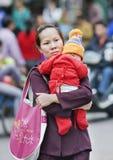 Mère chinoise avec son enfant au centre de la ville, Sanya, Chine Photos stock