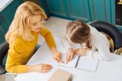 Mère concentrée aidant son enfant avec ses devoirs Photo stock