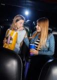 Mère consolant la fille effrayée dans le théâtre de cinéma Image stock