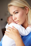 Mère déprimée caressant le bébé nouveau-né image libre de droits