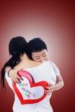 Mère d'étreinte de garçon tenant la carte d'amour Photo stock