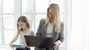 Mère d'affaires avec l'ordinateur portable et la fille s'asseyant par la fenêtre photos libres de droits
