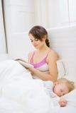 Mère dans le livre du relevé de chambre à coucher tandis que sommeil de chéri Photographie stock libre de droits
