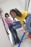 Mère de aide de fille dans le plancher de nettoyage photographie stock