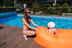 Mère de beauté avec le petit fils par la piscine photos libres de droits