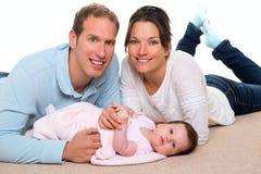 Mère de chéri et famille heureuse de père se trouvant sur le tapis Photographie stock