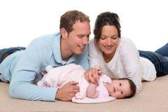Mère de chéri et famille heureuse de père se trouvant sur le tapis Photos stock