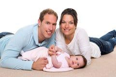 Mère de chéri et famille heureuse de père se trouvant sur le tapis Photo libre de droits