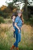 Mère de cow-girl portant sa petite fille dans une bride de bébé photos stock